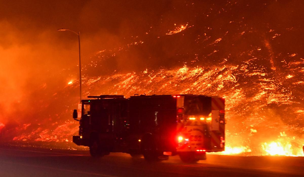 One man dies as wind-driven Los Angeles wildfire forces 100,000 to flee